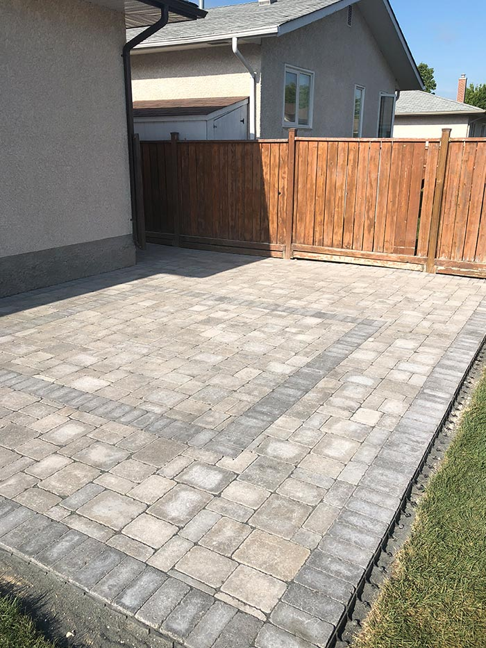 Custom interlock patio for fenced-in residential backyard