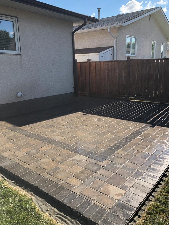 interlock stone patio in a fenced-in back yard