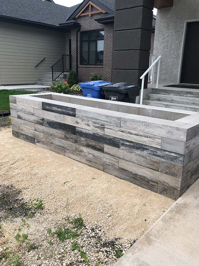 Expert interlock long narrow planter outside of a new home