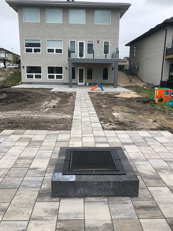 Expert interlock fire pit and long walkway complete for the backyard of a new home