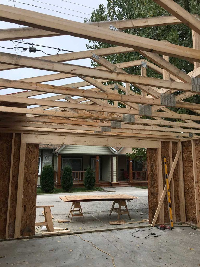 a residential garage in the process of being built with wooden roof beams
