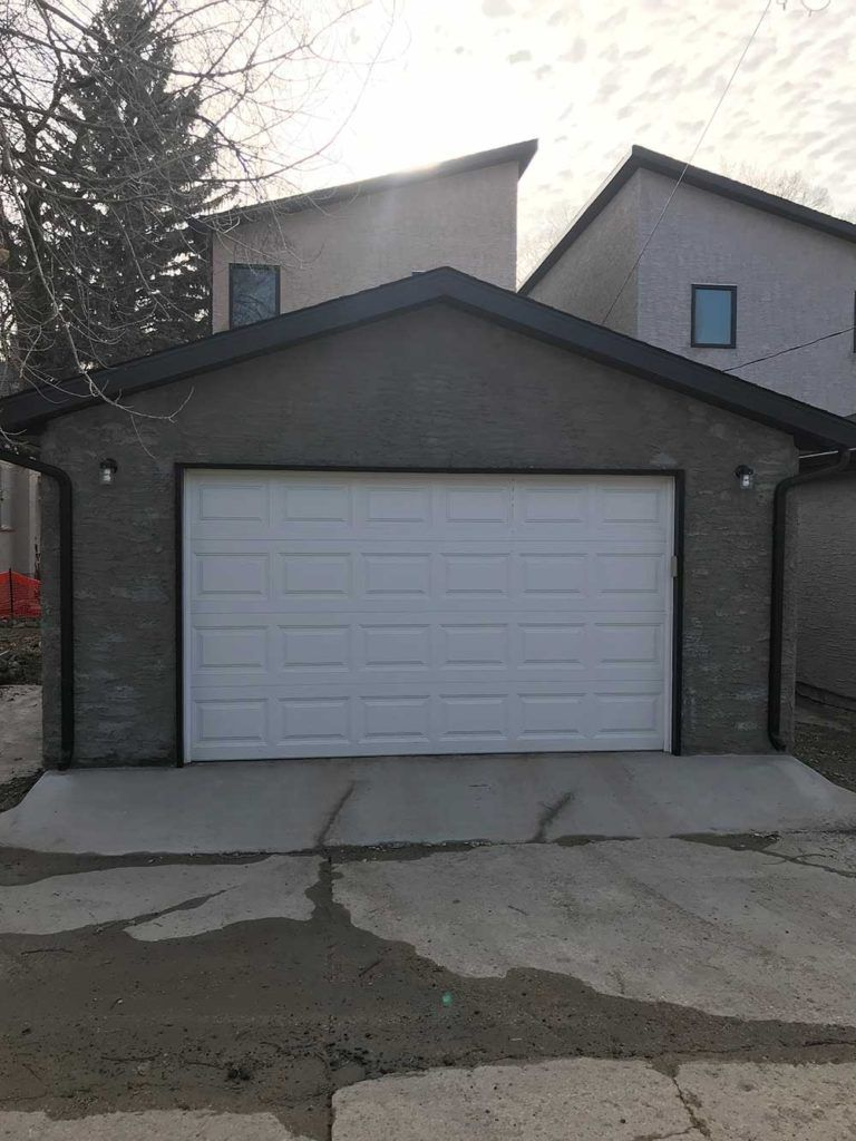 a newly built residential garage with a white garage door and stone walls