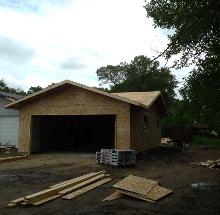 a residential garage build in progress with completed wood walls and roof
