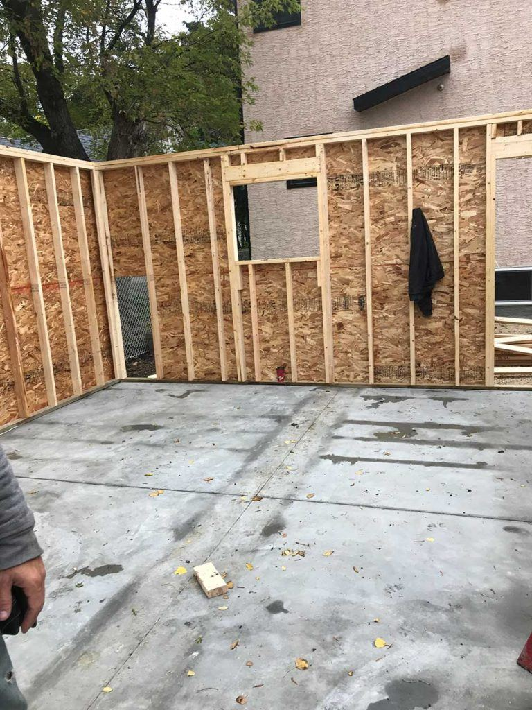 a residential garage build in process with a stone floor and framed wooden walls