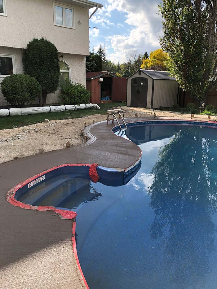a kidney shaped in-ground pool during installation with a new concrete deck